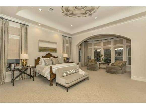 The primary bedroom offers a comfy bed on the carpet flooring, and stunning tray ceiling and an open archway that defines the sitting area.