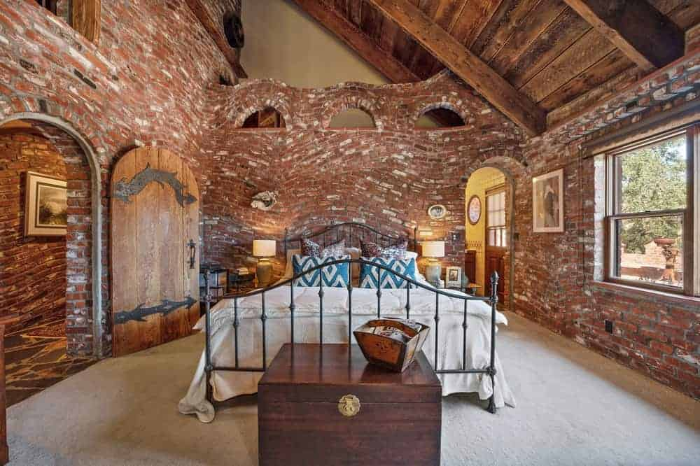 The primary bedroom has cozy red brick walls and matching rustic arched wooden door fitted with dark iron that matches the wrought iron frame of the massive bed.