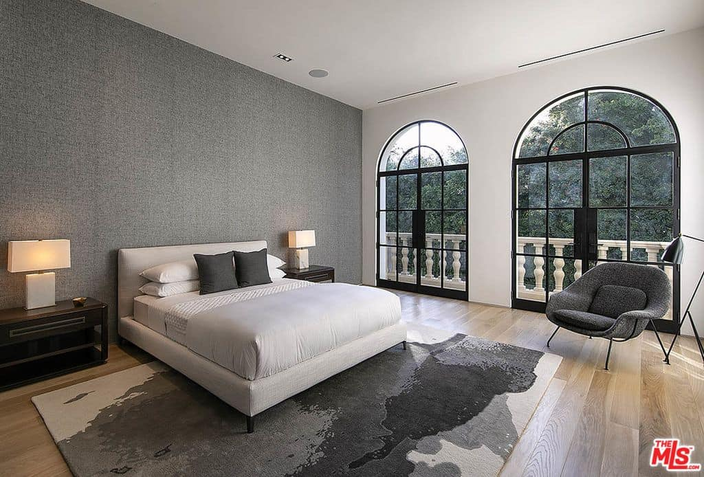 Large and stylish guest bedroom with wood flooring, modern reading chair with two double arched glass doors leading balcony