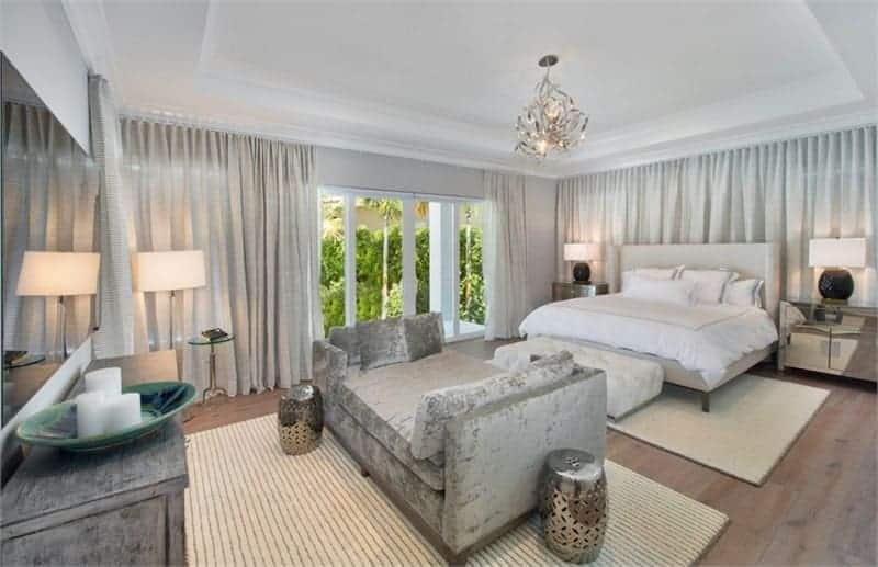 This primary bedroom offers a gray wingback bed and a cozy seat in front of the tv hanging on the wall. It also has a stunning chandelier and a sliding door that leads to the balcony