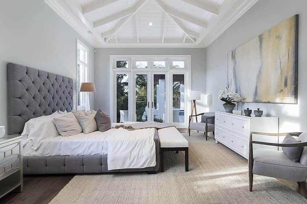 The primary bedroom features a large bed with a gray cushioned headboard topped and a high vaulted ceiling with exposed beams.