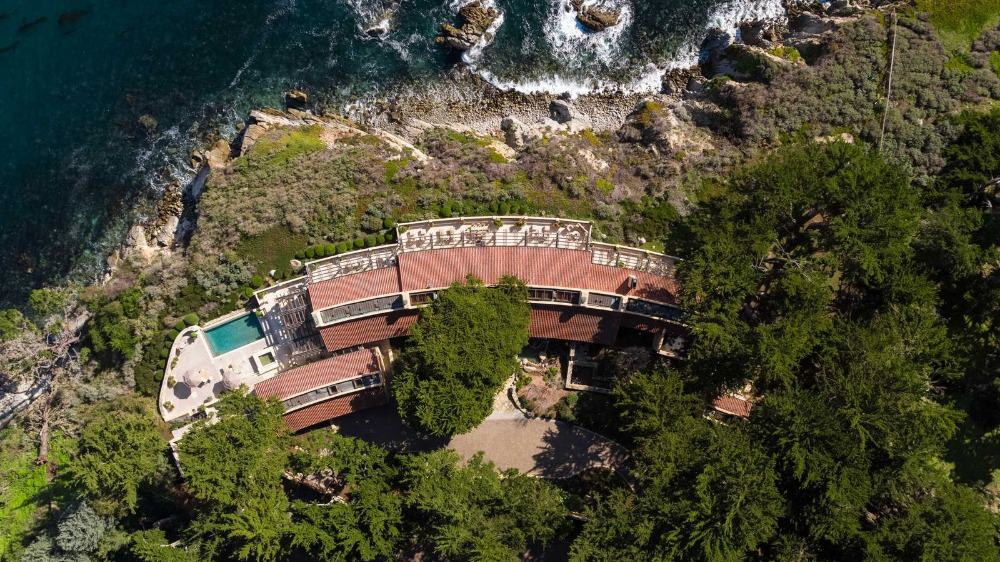 Bird's eye view of the property boasting the dramatic sea and landscape surroundings. Images courtesy of Toptenrealestatedeals.com.