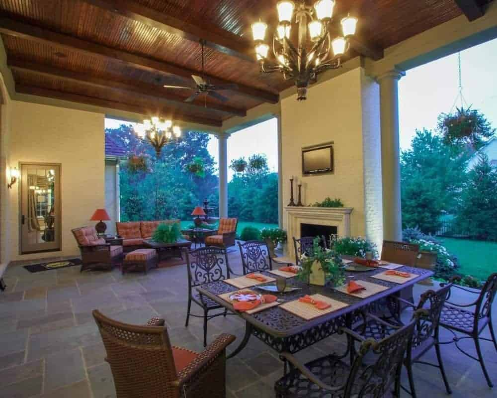 This relaxing covered patio features a comfy couch lit by stunning chandelier and it has a fireplace and metal dining table set with chairs.