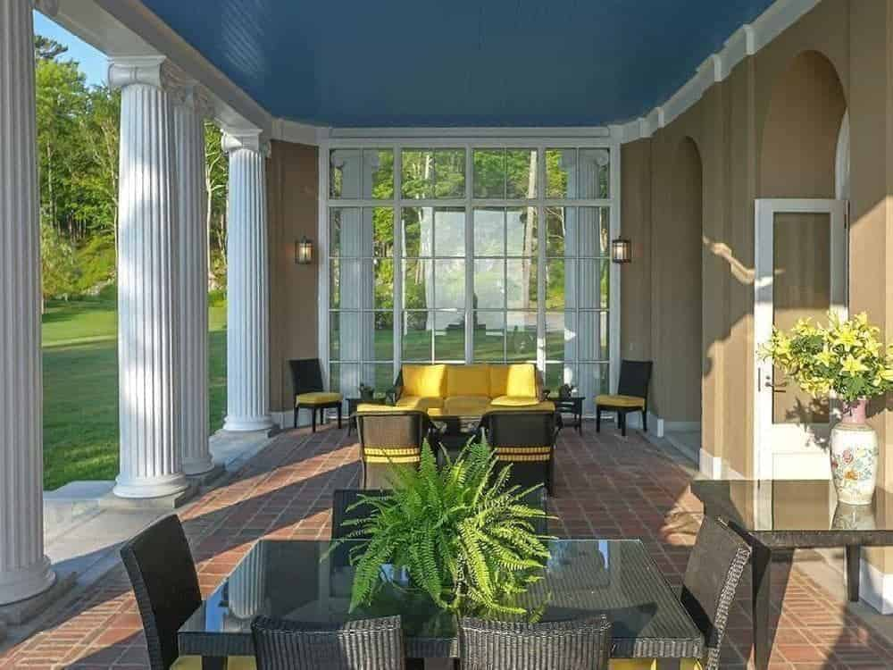 This elegant covered patio features a comfortable sitting area with yellow cushioned furniture and a dining table set in the side.