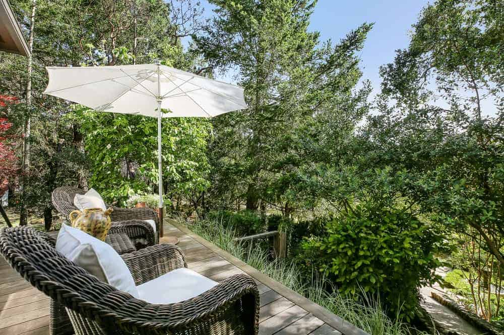 This balcony and patio had a couple of comfortable woven wicker armchairs with cushions facing the beautiful treetop view of the surrounding landscape.