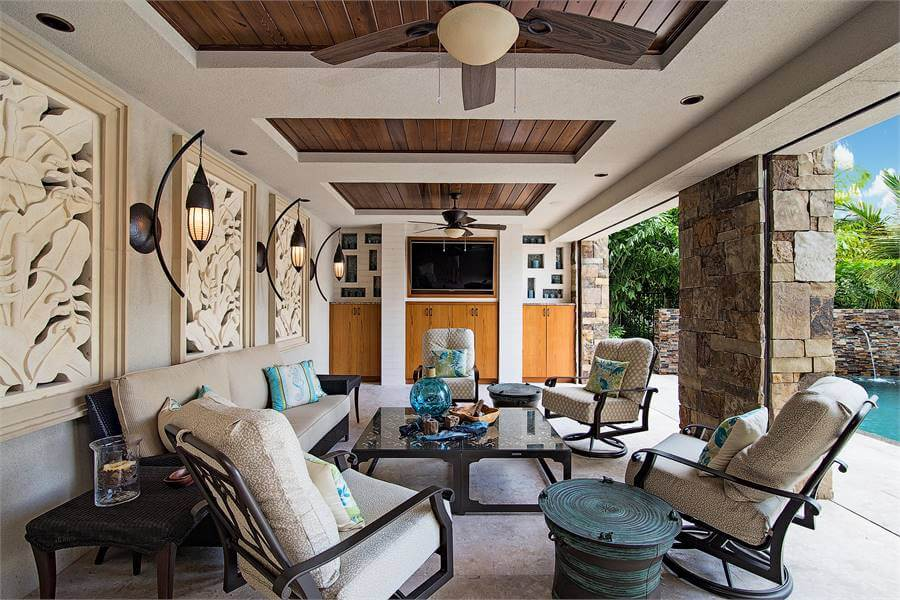 This patio offers an enclosed in wood-framed plate roof, stone columns, and beige dividers embellished by confined works of art and warm sconces.