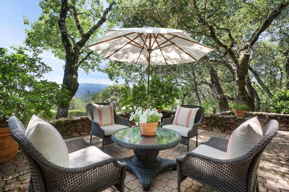 This gorgeous patio is an ideal spot for a morning coffee with its overhang of tall trees, padded outdoor seats, and a glass-top round table.