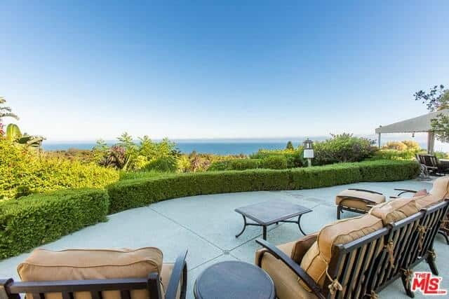 This backyard area features brown chairs with a wooden table in front of the beach view.