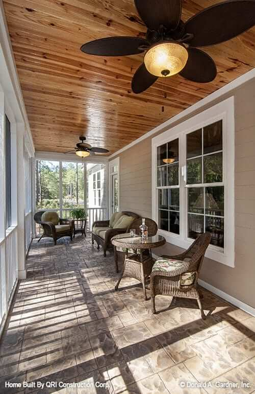 This porch is framed with white railings and decorative columns and wicker seats and warm ceiling fans complete the screened porch.