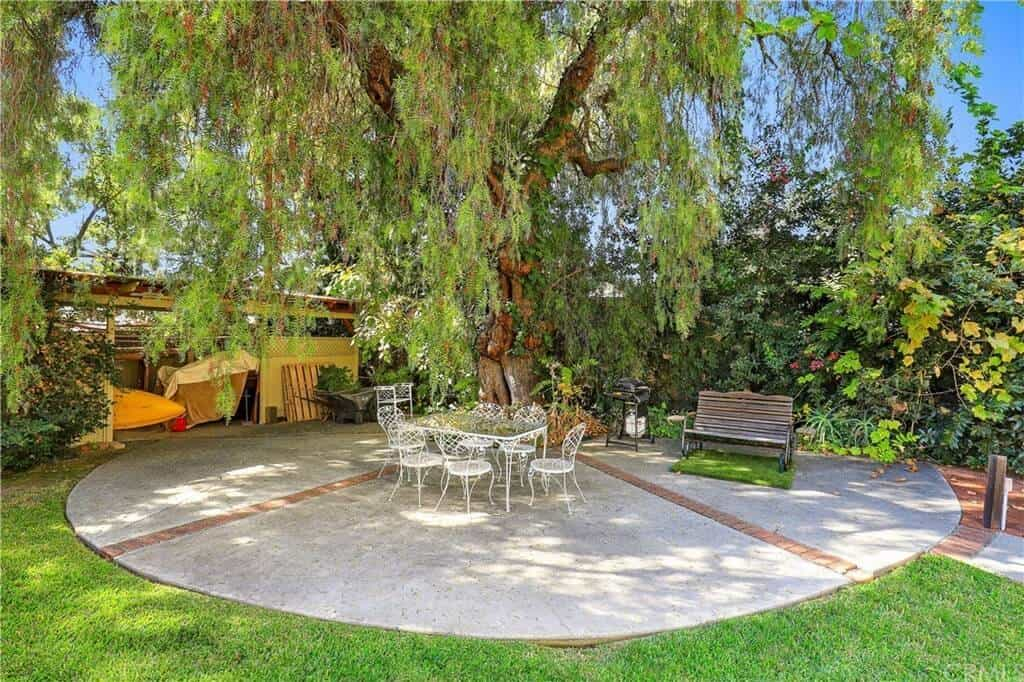 This backyard area features a rectangular glass table paired with metalic white chairs that matches the beautiful trees.