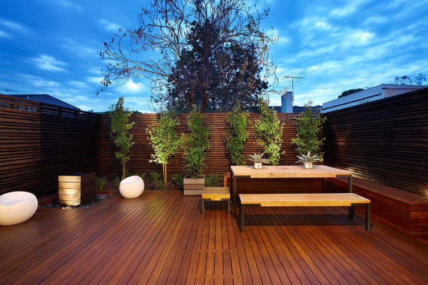 The patio is an exercise in rich minimalism, with sumptuous timber flooring and privacy fending that wraps the entire space, dotted with manicured plant life.