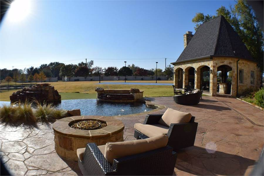 This swimming pool area features a fire pit and cozy chairs on the marble tiled flooring and a gazebo.