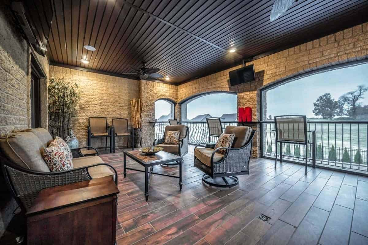 The balcony has wicker seats, wide board deck and brick walls mounted with TVs and wooden ceiling with recessed lights.