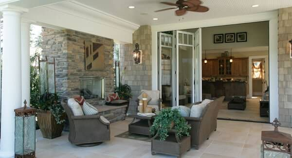 This patio has a comfy gray seat with a coffee table on the rug and a stone fireplace that matches the walls.