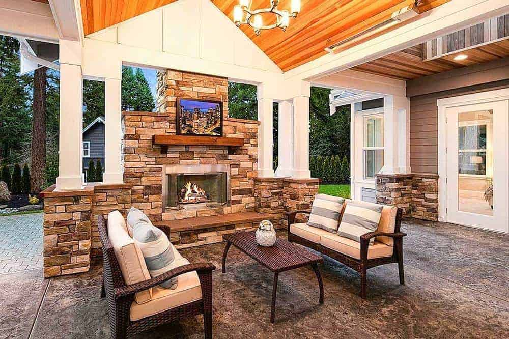 The charismatic and relaxing patio is secured with a wooden high vaulted ceiling with a chandelier that balances a crystal fixture over the outdoor couch set and a small table.
