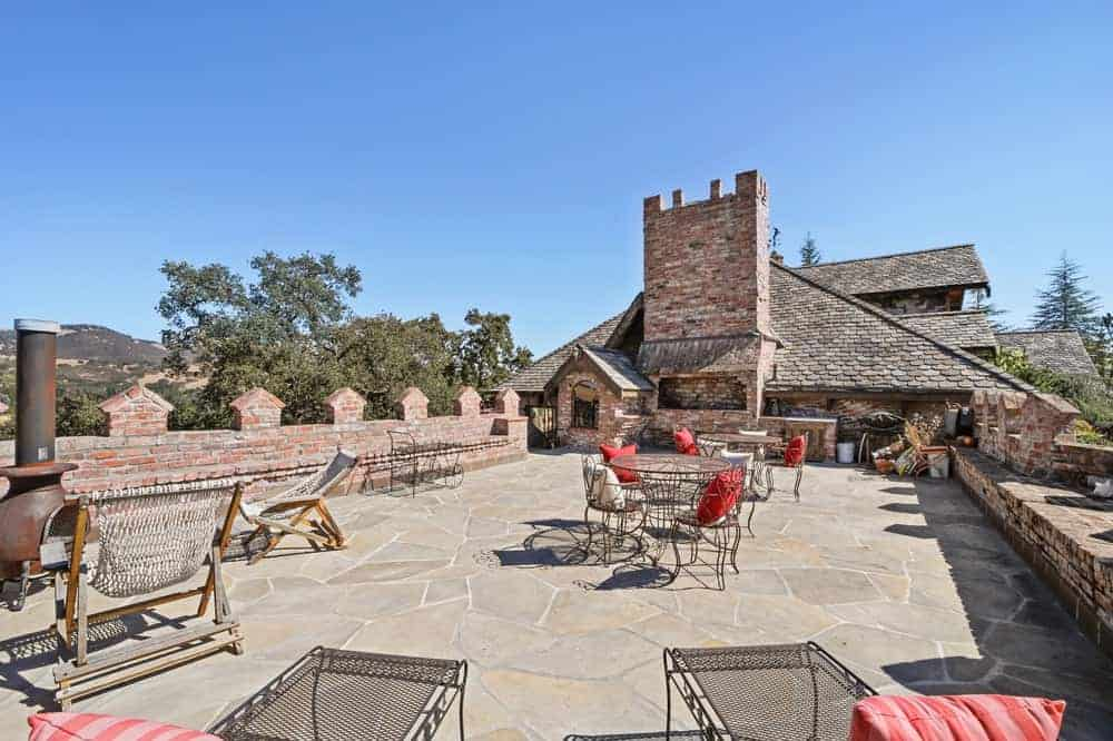 The rooftop patio has a wide stone floor space with an outdoor cooking area, outdoor dining area and a sitting area that is warmed by a freestanding iron furnace.
