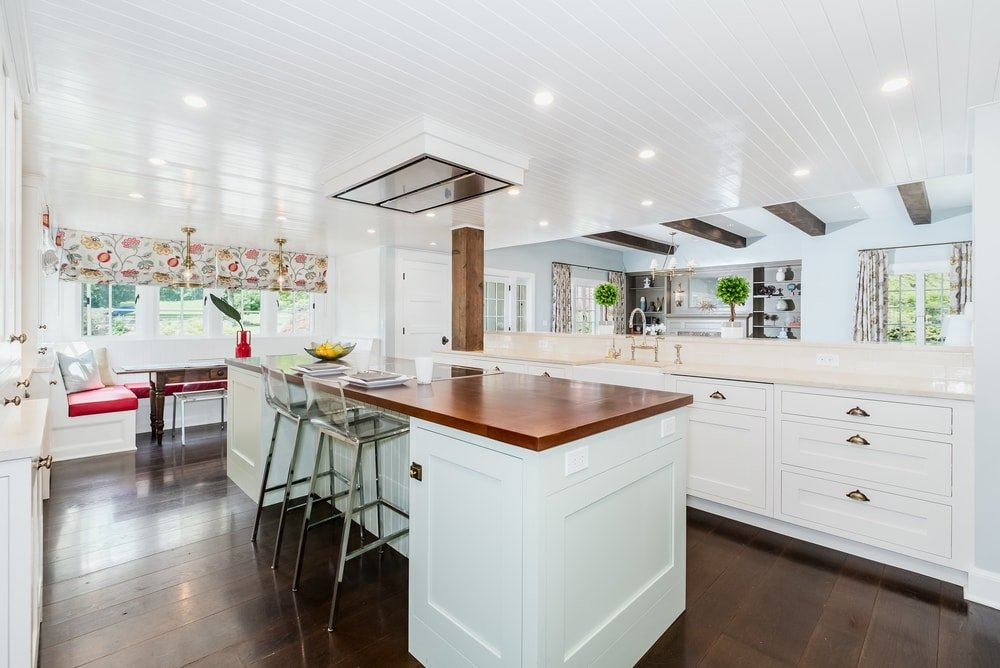 The kitchen has bright and white shaker cabinets and drawers complemented by the hardwood flooring and the wood countertop of the kitchen island. You can see here that there is a thick wooden pillar at the corner that connects the counter with the ceiling.