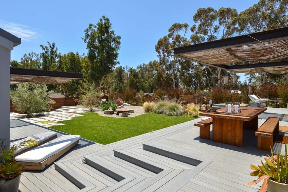 This covered dining area is placed on a wooden deck with steps leading down to the lush grass lawn.