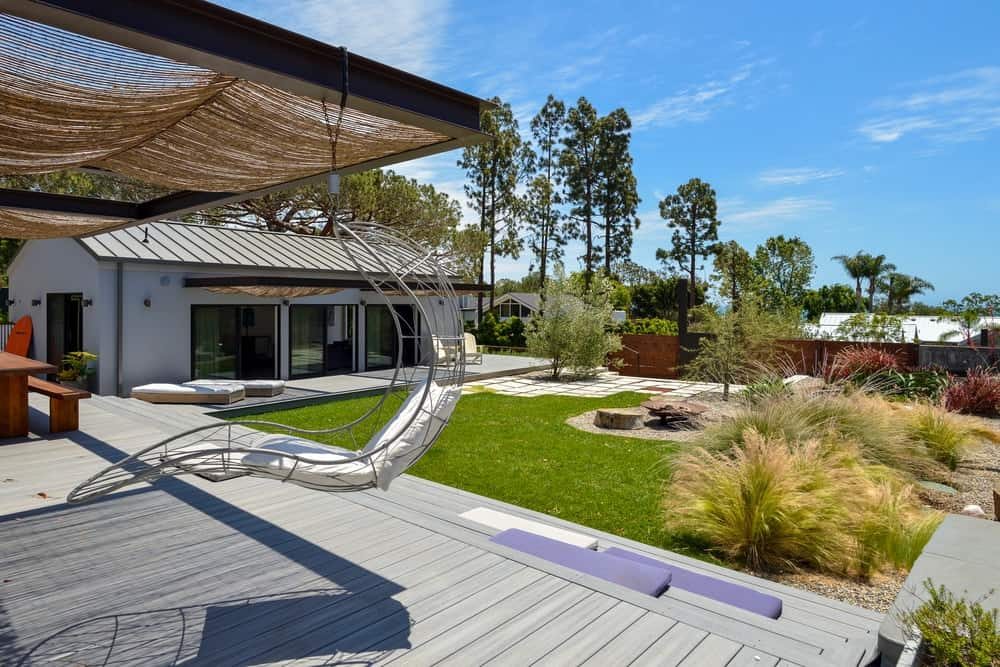 The edge of this covered area has a modern hanging chair with a great view of the lush landscaping of the grounds.