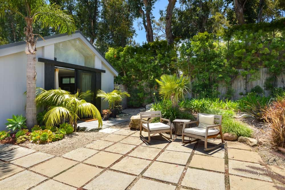 One side of the house has a stone slab flooring complemented by the tropical plants on the sides that serves as a lovely background for the sitting area.