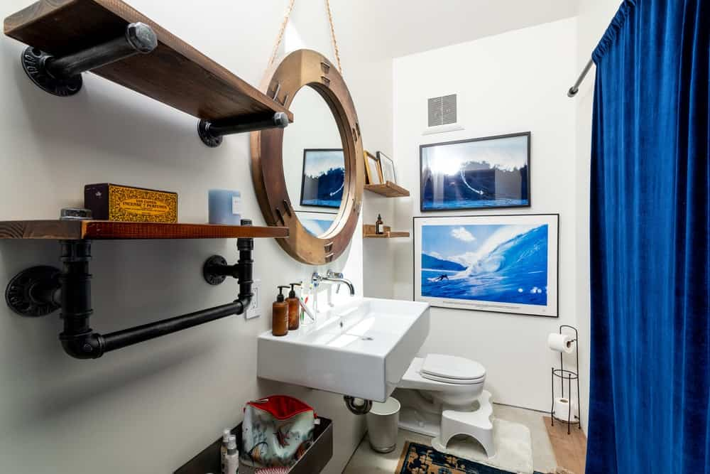 This charming bathroom has a round wood-framed mirror that matches with the floating wooden shelves.