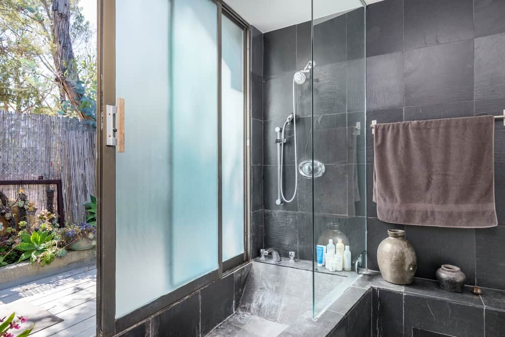 This bathroom's shower area has a set of sliding glass windows that has frosted glass panels for privacy.