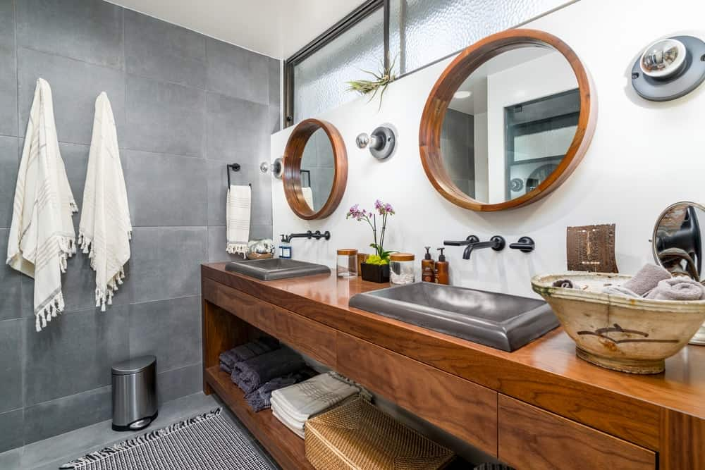 The bathroom has a large wooden vanity with two sinks that stand out against the wooden countertop. This matches with the pair of wall-mounted mirrors.