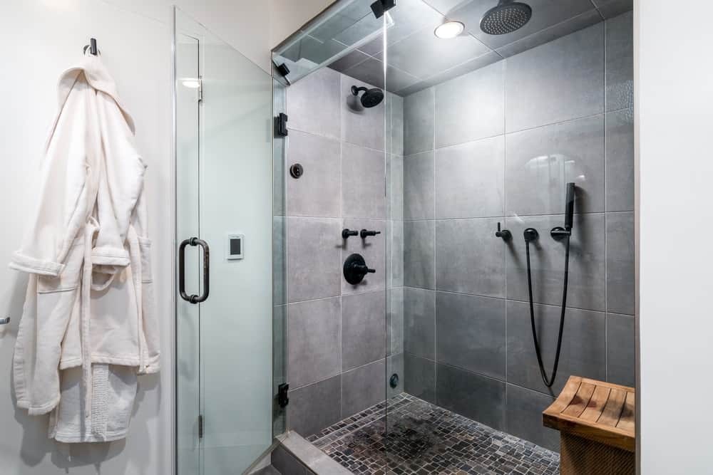 This other bathroom has a large glass-enclosed shower area with gray tiles on its walls and ceiling.