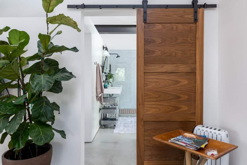 This other bathroom has a rustic feel to its sliding wooden door mounted on wrought iron supports.