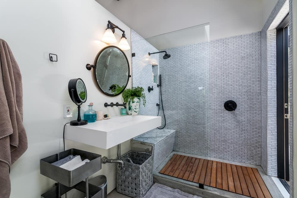 The bright walls that match with the floating sink contrasts the black the faucets and fixtures of the bathroom that has a wooden flooring to its shower area.