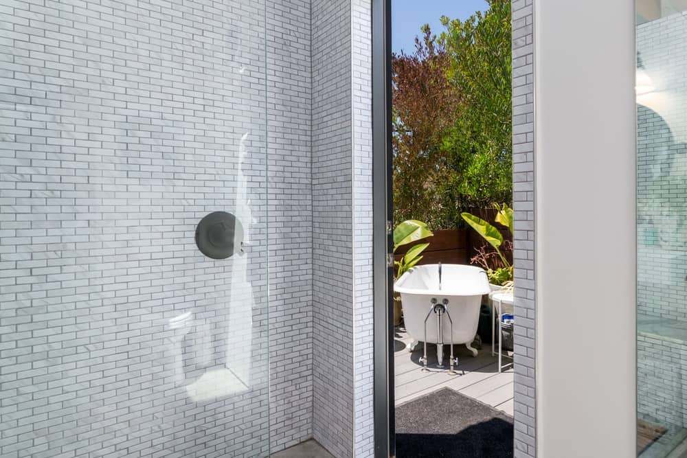 From this shower area is an opening that leads to the freestanding outdoor bathtub in the middle of a garden.