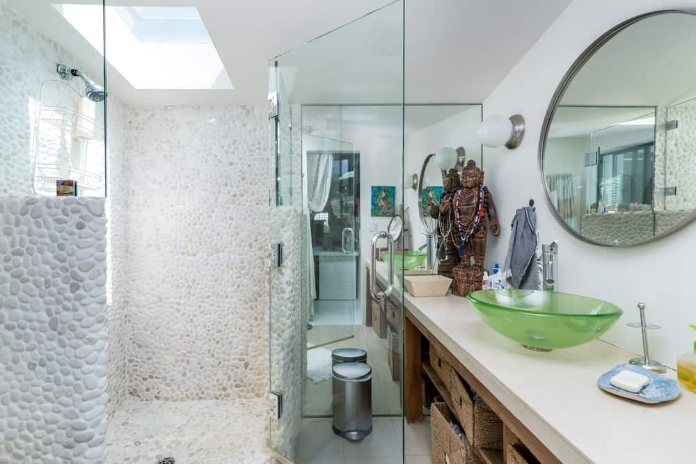 The glass-enclosed shower area of this other bathroom is topped with a charming sky light that brightens the light tone of the bathroom walls.