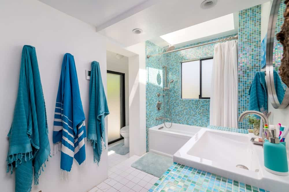 These green tiles stand out in contrast to the bright white walls and ceiling of the bathroom.
