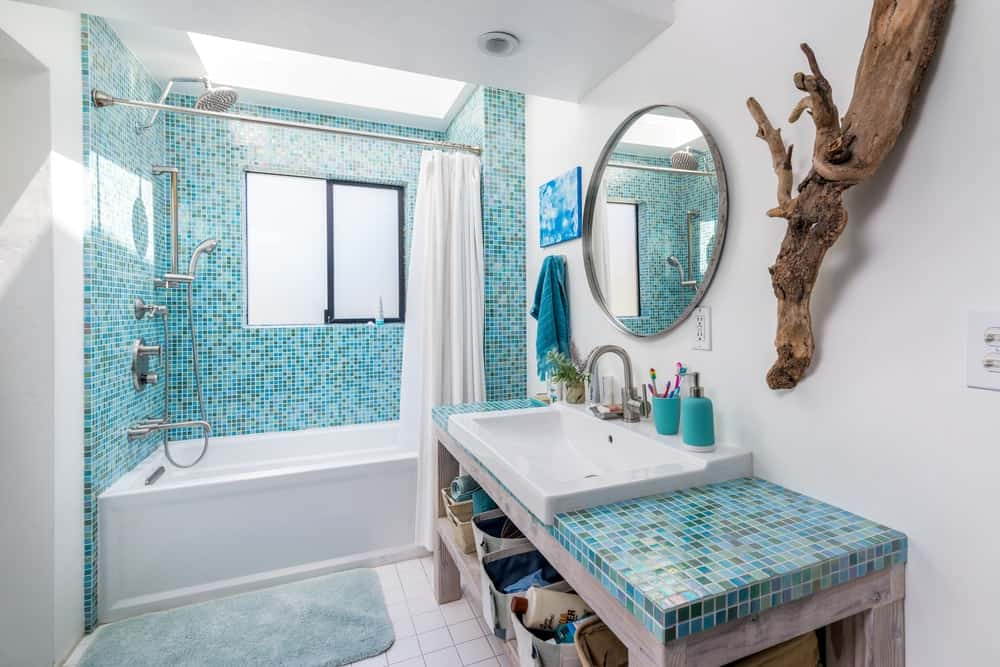This gorgeous bathroom is complemented by the green tiles applied to its vanity countertop and shower area walls.