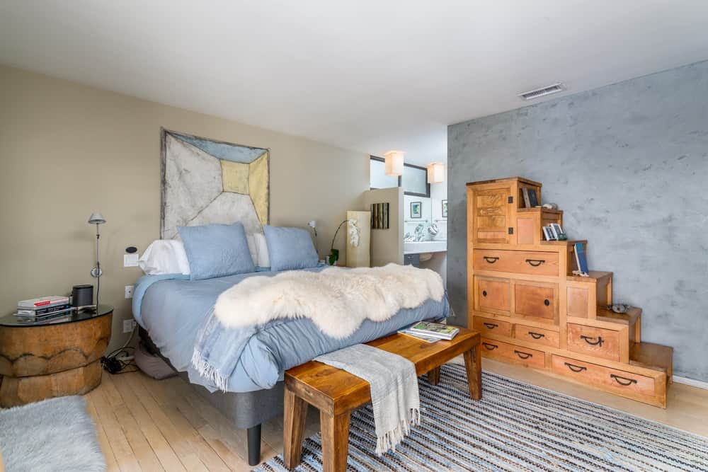 The blue sheets and pillows of the bed is complemented by the wooden bench at the foot of the bed matching with the wooden cabinetry on its side.