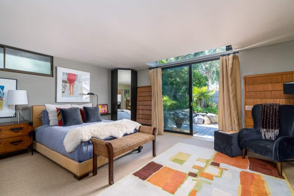 The beautiful platform bed is complemented by a brown cushioned bench at the its foot as well as a colorful area rug that covers the light hardwood flooring.