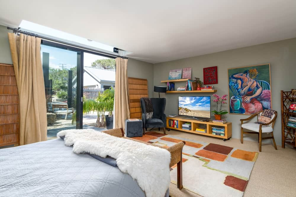 This other bedroom has a larger floor space with a an entertainment system on the far wall across from the bed.