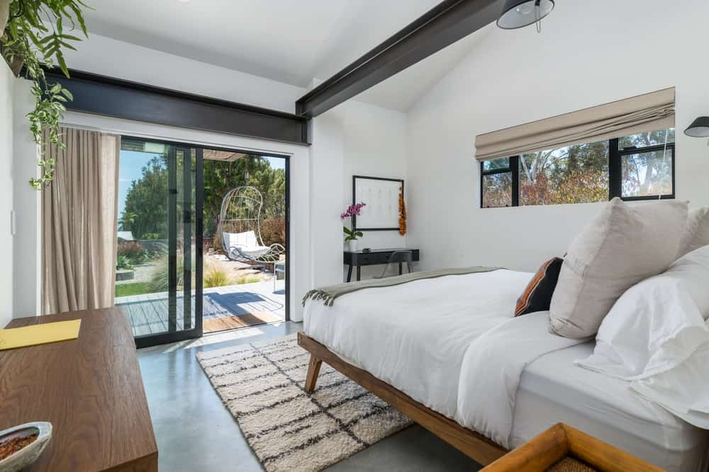 Across from the bed is a set of large sliding glass doors that bring in natural lighting.