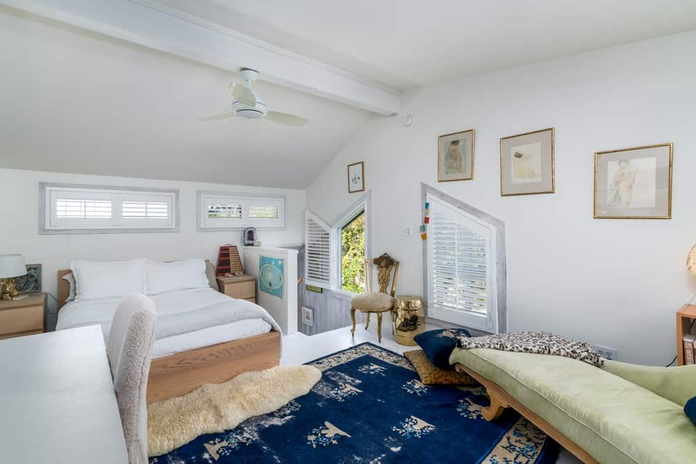 The white walls and white arched ceiling of this bedroom matches with bed and contrasted by the brilliant blue area rug.