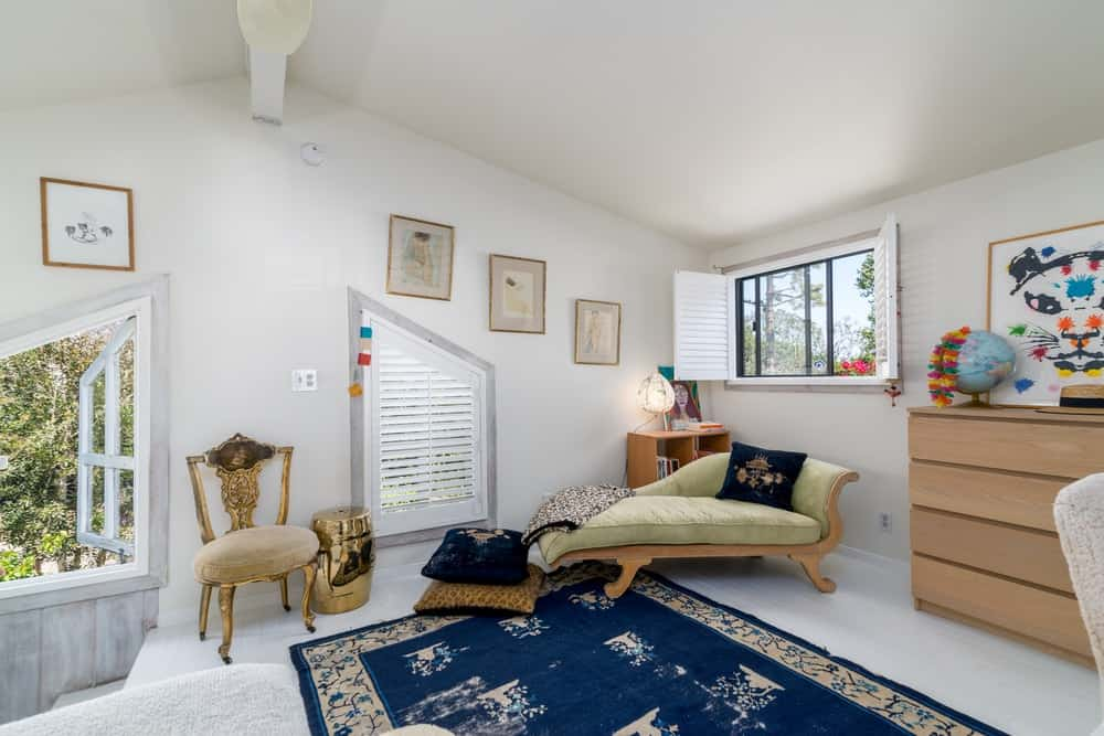 By the edge of this area rug is a day-bed placed under the window for a cozy reading nook.