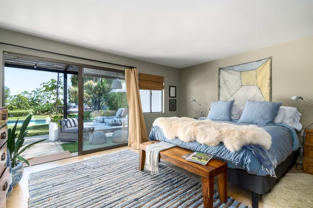 This simple and cozy bedroom is brightened by the large sliding glass doors with access to the backyard.