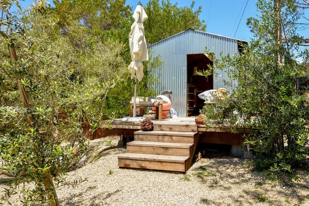 The pebbled walkway also leads to the ceramics shed placed on an elevated platform paired with wooden steps.