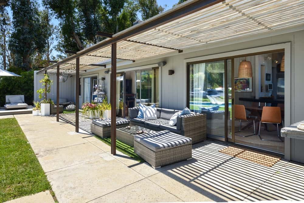 The poolside area has a covered patio with a comfortable sofa set facing the pool.