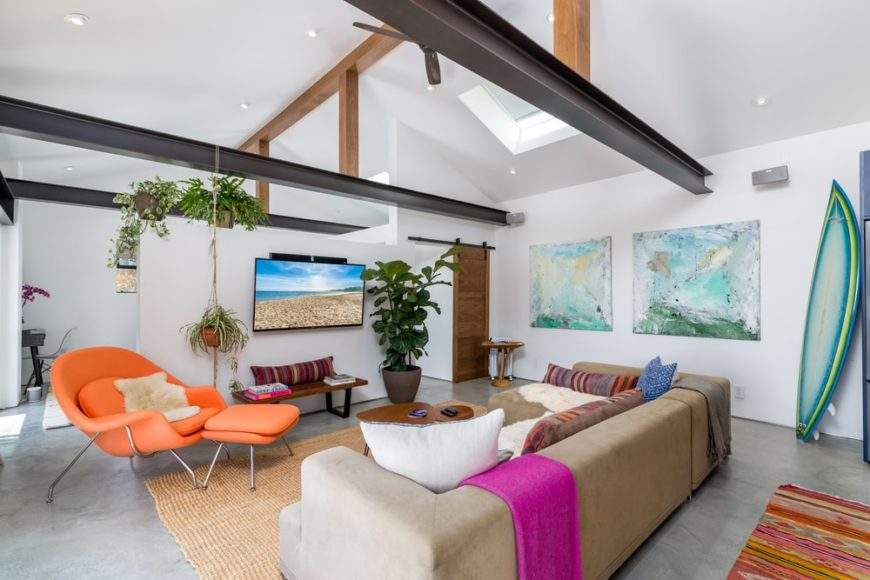 This is a charming media room with a tall white cove ceiling brightened by a skylight and contrasted by exposed wooden beams.