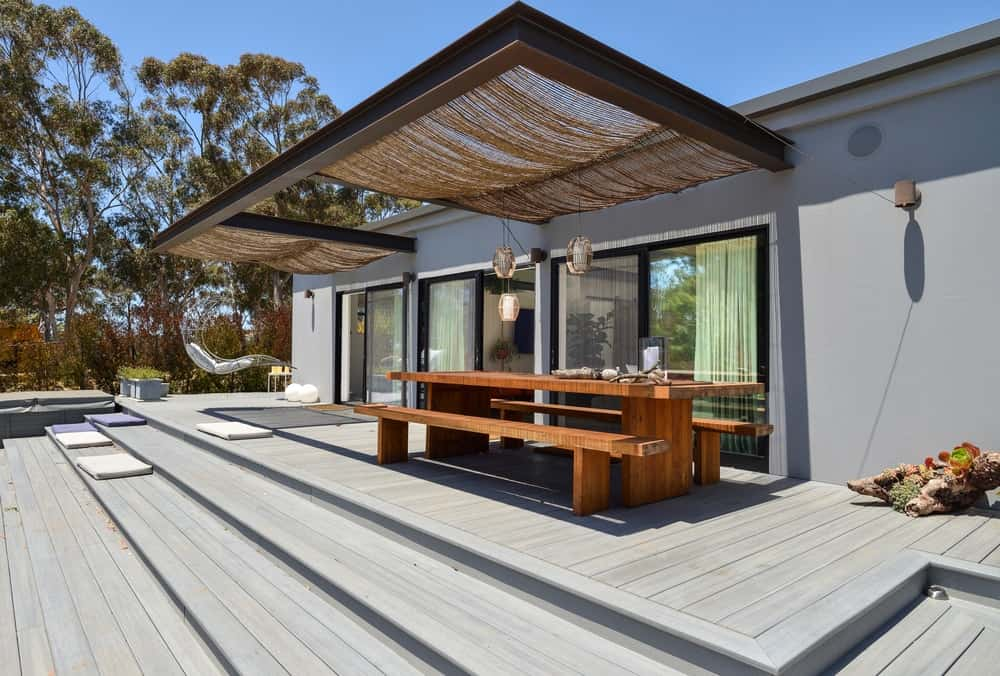 Just outside the house is a charming outdoor dining area that has a long wooden dining table paired with a couple of wooden benches.