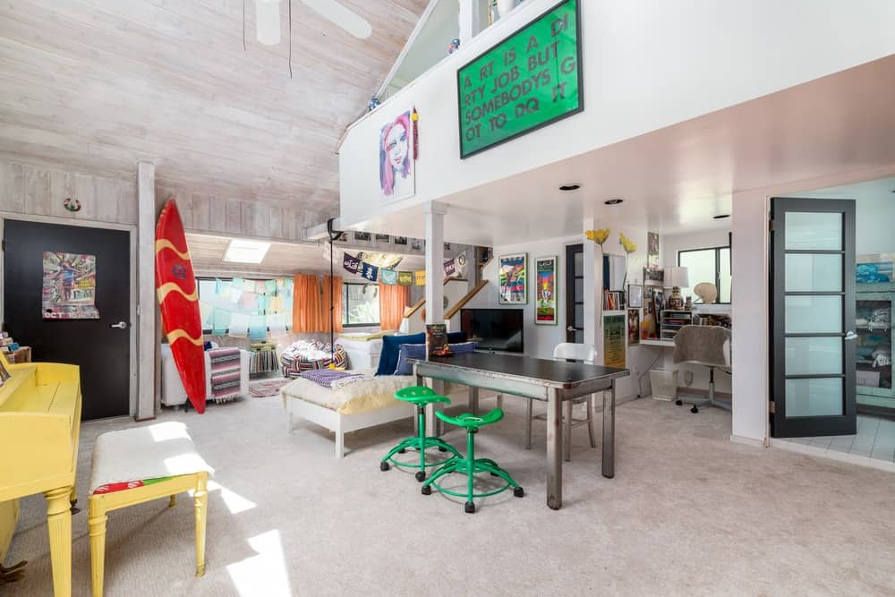 This large bedroom has various amenities and relaxation areas adorned by colorful decors to stand out against the white walls and tall wooden ceiling.