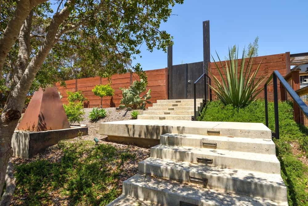 This is a charming entrance to the enclave with a set of stone steps and a black wooden gate.