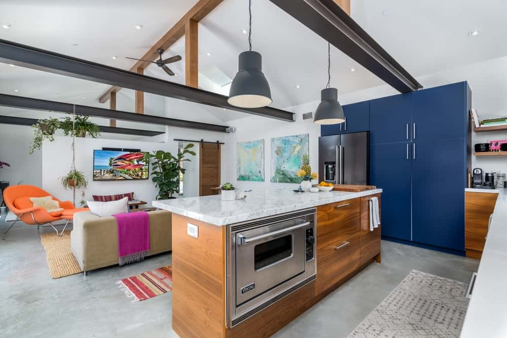 The kitchen of this house has a large wooden kitchen island that houses the stainless steel oven topped with a white countertop.