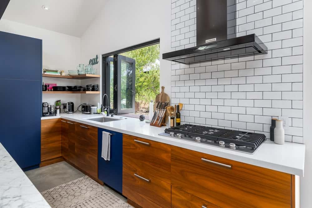 This countertop matches well with the wooden cabinetry lining the walls complemented by subway tiles for a backsplash of the cooking area.