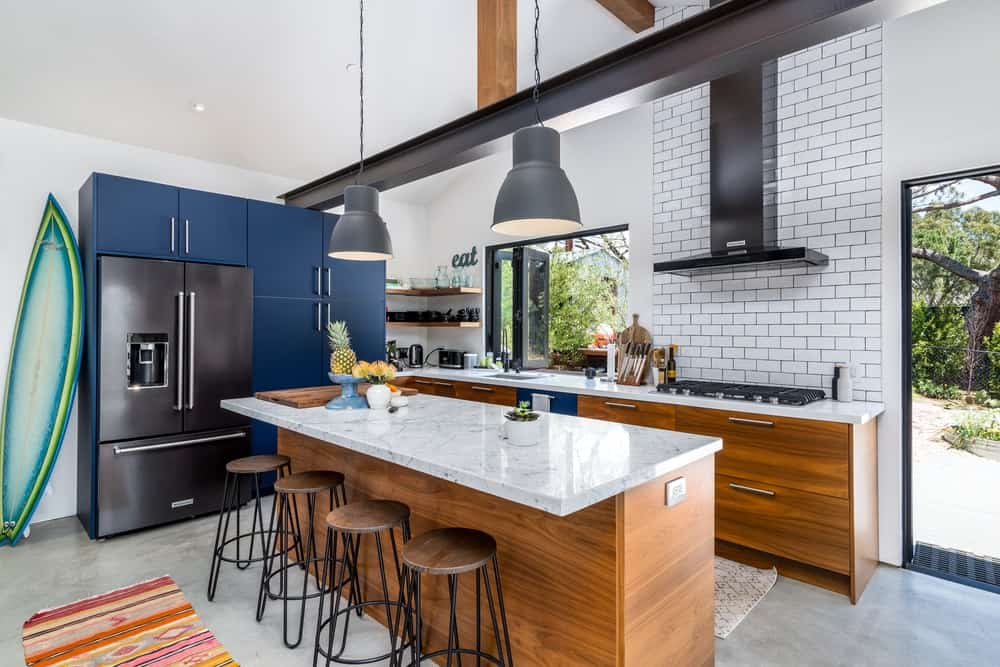 By the edge of the cabinetry is the matte blue structure of cabinets that houses the fridge.
